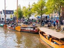 Mensen en historische boten in oude haven tijdens de Dagen van gebeurtenisadmiraliteit, Dokkum, Friesland, Nederland stock afbeelding