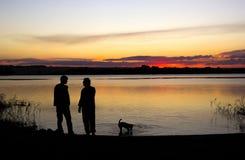 Mensen en hondsilhouet bij zonsondergangmeer Stock Afbeelding