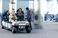 Mensen en passagiers die in gemotoriseerde karren in de luchthaven berijden Royalty-vrije Stock Afbeeldingen