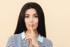 Mensen en stilteconcept Het aantrekkelijke wijfje met stilteteken houdt voorvinger op lippen, vraagt stil te zijn aangezien ieman stock fotografie
