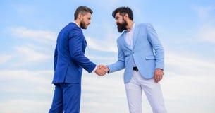 Mensen formele kostuums die achtergrond van de handen de blauwe hemel schudden Goedgekeurd transactie toegelaten door beide partn royalty-vrije stock foto