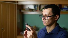 Mensen gebrilde glazen die een bericht op telefoonsmartphone typen sociale media stock videobeelden