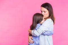 Mensen, geluk, liefde, familie en gelukkig moederschapconcept - weinig dochter die en haar moeder over roze koesteren kussen royalty-vrije stock foto