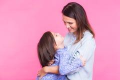 Mensen, geluk, liefde, familie en gelukkig moederschapconcept - weinig dochter die en haar moeder over roze koesteren kussen stock fotografie