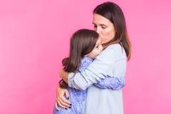 Mensen, geluk, liefde, familie en gelukkig moederschapconcept - weinig dochter die en haar moeder over roze koesteren kussen royalty-vrije stock foto's