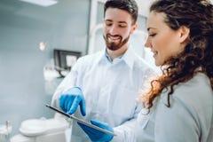 Mensen, geneeskunde, de stomatologie en gezondheidszorgconcept - gelukkige mannelijke tandarts die de computer van tabletpc tonen stock foto's