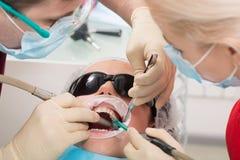 Mensen, geneeskunde, de stomatologie en gezondheidszorgconcept - mannelijke tandarts en medewerker die met speekseluitwerper wijf stock foto's