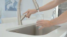 Mensen gietend water van de tapkraan in glas stock videobeelden