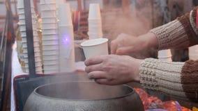 Mensen gietende kokende drank in glazen en het geven aan iedereen, liefdadigheid stock footage