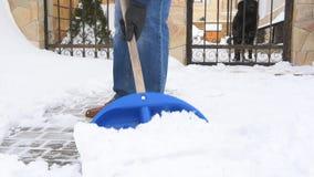 Mensen gravende sneeuw met schop dichtbij huis stock video