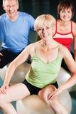 Mensen in gymnastiek op oefeningsbal royalty-vrije stock afbeelding