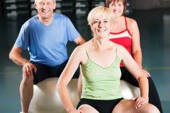 Mensen in gymnastiek op oefeningsbal Stock Afbeelding