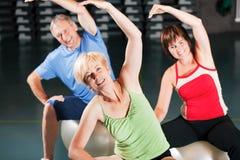 Mensen in gymnastiek op oefeningsbal Stock Foto