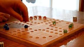 Mensen het gebruiken olored marmer en dobbelt om een familiespel op een eigengemaakte raad te spelen stock videobeelden