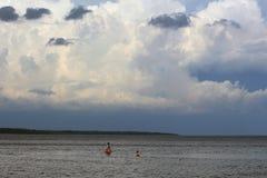 Mensen in het overzees vóór het onweer Stock Fotografie
