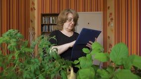 Mensen, het tuinieren, bloemen en beroepsconcept - sluit omhoog van vrouw of tuinman met de computer van tabletpc stock videobeelden