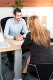 Mensen knappe werkgever die jonge meisjesmanager bekijken met glimlach terwijl het luisteren aan haar verklaringen van rapport stock afbeelding