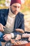 Mensen kokend vlees bij de houtskoolgrill Stock Foto