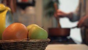 Mensen kokende maaltijd in pot op fornuis in keuken beweegt houten lepel stock footage