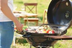 Mensen kokende vlees en groenten bij de barbecuegrill Stock Afbeelding