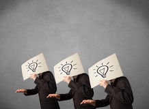 Mensen in kostuum het gesturing met geschetst lightbulbs op karton Stock Fotografie