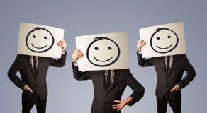 Mensen in kostuum het gesturing met geschetste smileygezichten op karton royalty-vrije illustratie