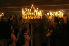 Mensen lichte kaarsen tijdens feestelijk gebed in kerk Stock Fotografie