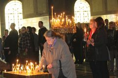 Mensen lichte kaarsen tijdens feestelijk gebed in kerk Royalty-vrije Stock Afbeeldingen