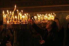 Mensen lichte kaarsen tijdens feestelijk gebed in kerk Stock Afbeeldingen