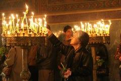 Mensen lichte kaarsen tijdens feestelijk gebed in kerk Royalty-vrije Stock Foto