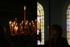 Mensen lichte kaarsen tijdens feestelijk gebed in kerk Stock Foto