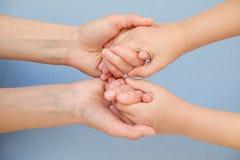 Mensen, liefdadigheid, familie en zorgconcept - sluit omhoog van vrouwenhanden houdend meisjeshanden stock afbeelding