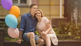 Mensen in liefdezitting op bank, de ballons van de kerelholding, onbezorgde romantische stemming Stock Afbeelding