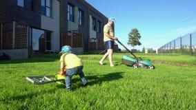 Mensen maaiend gazon met grasmaaimachine terwijl zoonsspel met stuk speelgoed grasmaaier gimbal stock videobeelden