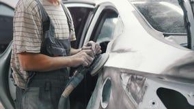 Mensen mechanische die poetsmiddelen in een zilveren autolichaam worden geschilderd met een molen stock footage