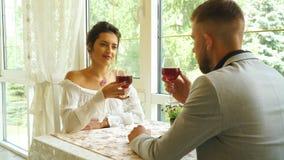 Mensen, mededeling en het dateren van concept - gelukkige paar het drinken wijn bij koffie stock videobeelden