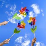 Mensen met kleurrijke windmolens Stock Afbeeldingen