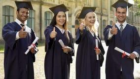 Mensen met universitaire diploma's in de academische diploma's van de regaliaholding, die duim-omhoog tonen royalty-vrije stock afbeelding
