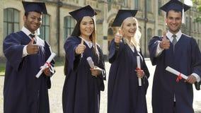 Mensen met universitaire diploma's in de academische diploma's van de regaliaholding, die duim-omhoog zetten stock videobeelden