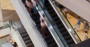 Mensen in motie in roltrappen bij het moderne winkelcomplex Mensen die in de hal meeslepen Het onduidelijke beeld van de motie Me stock video