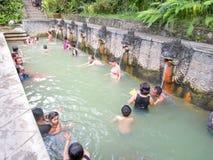 Mensen onder de waterstralen van de openbare pool Stock Afbeelding