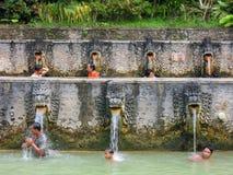Mensen onder de waterstralen van de openbare pool Royalty-vrije Stock Foto's