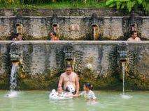 Mensen onder de waterstralen van de openbare pool Stock Fotografie