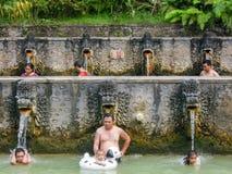 Mensen onder de waterstralen van de openbare pool Stock Foto