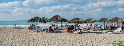 Mensen onder de zonlanterfanters die van riet op het strand rusten stock foto's