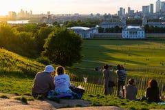 Mensen op de bovenkant die van de heuvel bij het Park van Greenwich, op de zonsondergang letten en foto's nemen Stock Afbeelding