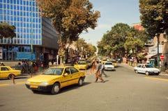 Mensen op de weg met lijn van taxiauto's in Iran Stock Fotografie