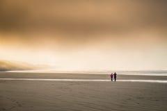 Mensen op een koud strand Stock Fotografie