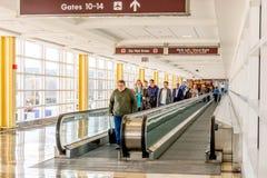 Mensen op een rollend trottoir in een heldere luchthaven Stock Foto