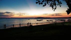 Mensen op het strand bij schemer met erachter boten stock footage